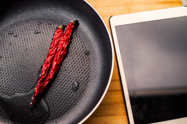 Chillies in a frying pan and tablet  Photo |  Download