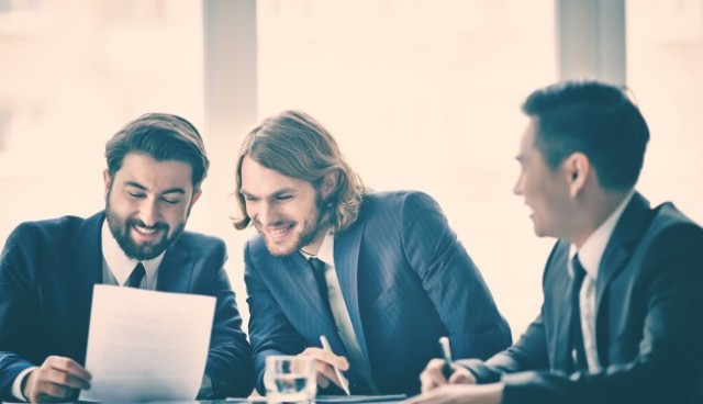 Co-workers reading a document and laughing  Photo |  Download